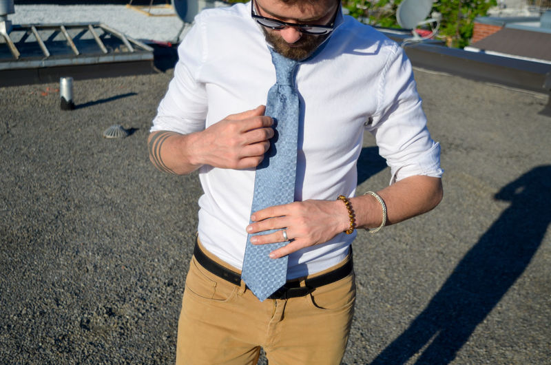 Close-up of man wearing necktie while standing outdoors