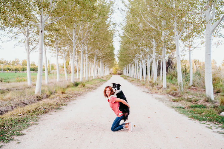 Woman carrying dog on road amidst trees in forest