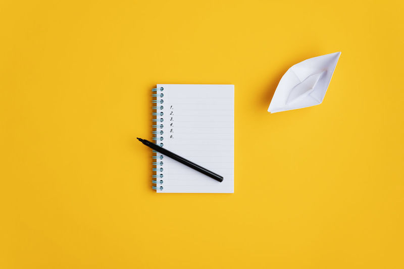 High angle view of pen against yellow background