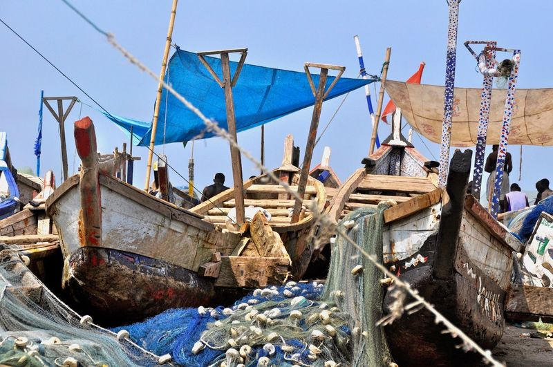 Fishing boats moored against blue sky