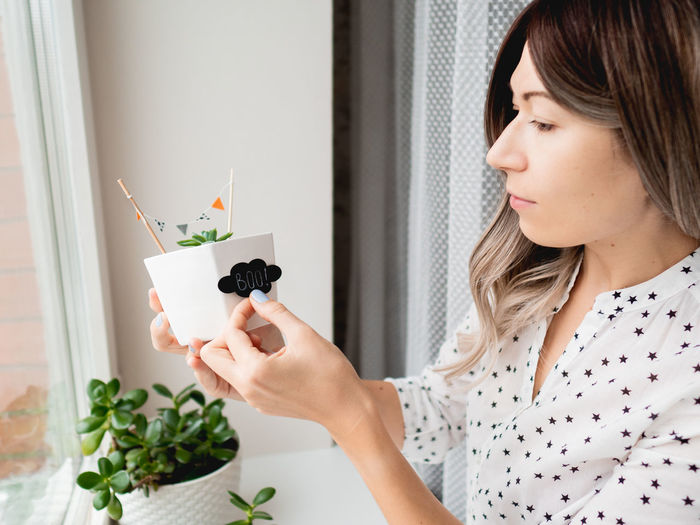 Portrait of young woman holding plant at home
