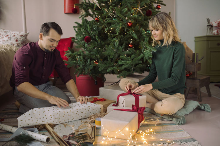 Couple packing gifts by christmas tree at home
