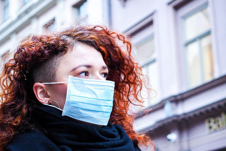Woman wearing mask looking away against building