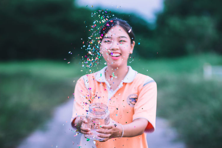 Smiling Young Woman Throwing Confetti