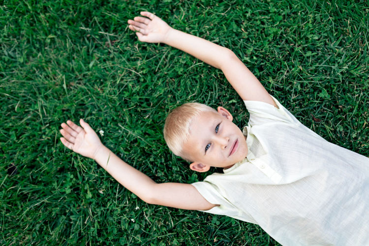 High angle view of baby lying on grassy field