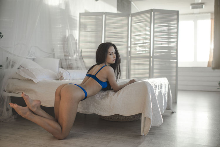 Sensuous female model wearing lingerie while kneeling against bed at home