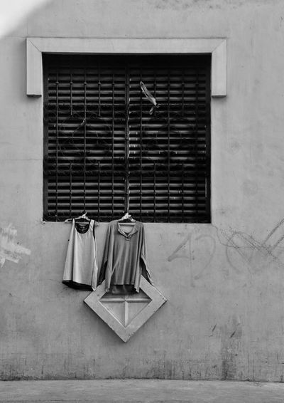 Low angle view of clothes hanging on coathangers at window