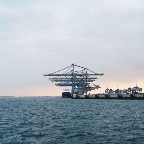 Cranes At Port In Sea Against Sky