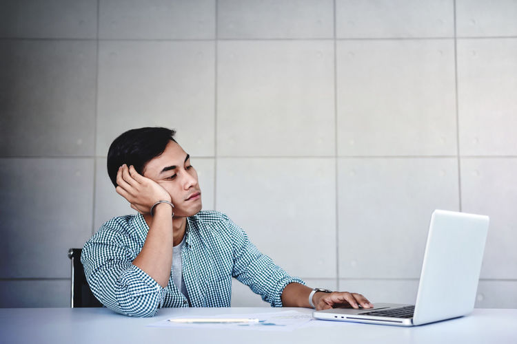 Tired and Stressed Young Businessman Sitting on Desk in Office with Computer Laptop. Exhausted Man Boring a Hard Work Tired Man Work Businessman Stressed Boring Bored Computer Business Office Headache Working Pressure Frustrated Sadness Sick Employee Failure  Confused Depressed Depression Laptop Unhappy Upset Vision Relaxation Young person Worker Frustration Male Sitting Asian  Hard Table Occupation Emotional Exhausted Concept Overworked Problems Men Job Using Laptop Technology