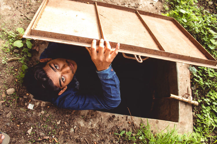 High Angle Portrait Of Teenage Boy Standing In Manhole