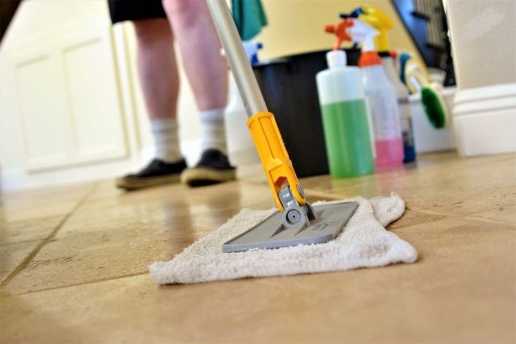 Low section of man cleaning floor at home