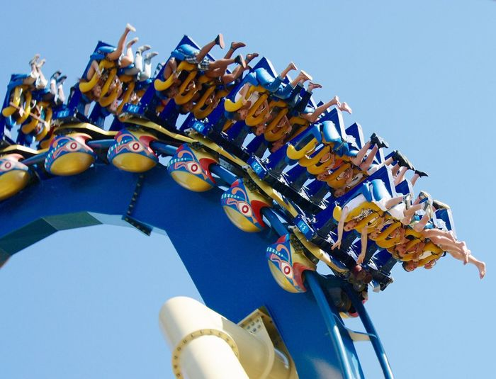 Low angle view of people on roller coaster ride against sky