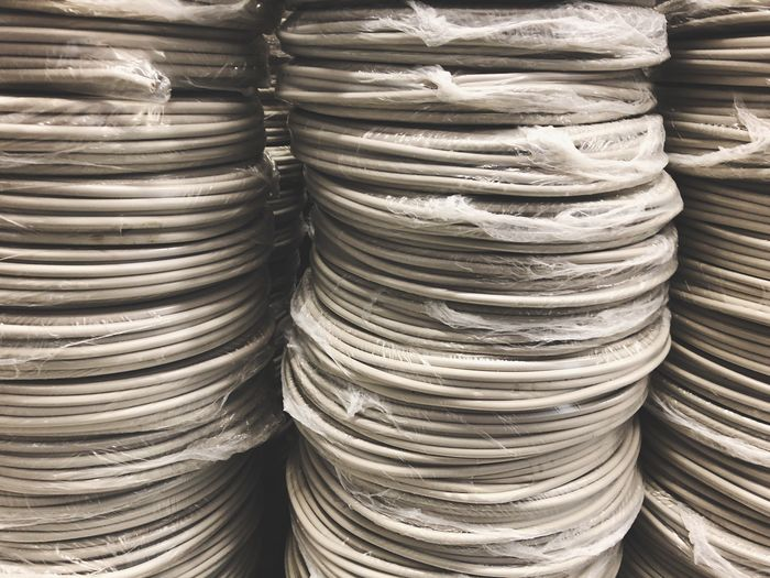 Gray stacked power capers Business Stacked Stack Plastic Cable Electricity  Copper  Packaging Plastic Hardware Store Construction For Sale Factory Stack Full Frame No People Large Group Of Objects Backgrounds Abundance Still Life