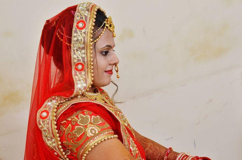 Close-up of bride wearing sari against wall