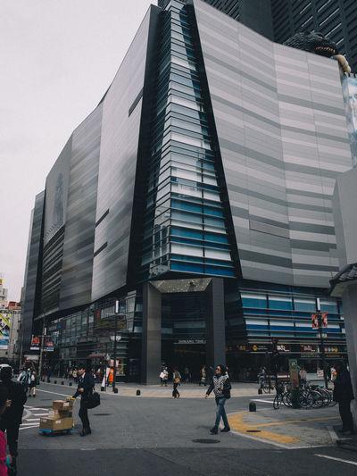 People walking on street by modern buildings in city