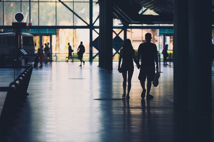 Silhouette couple holding hands while walking at railroad station