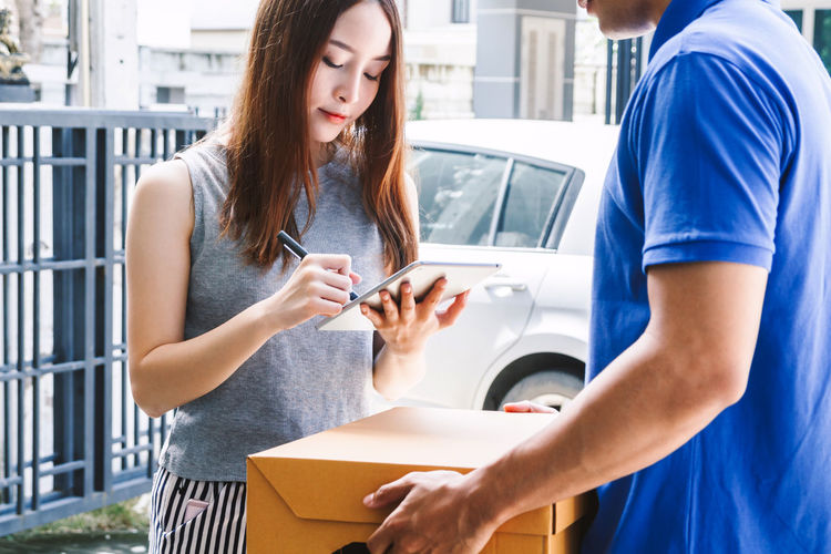 Woman putting signature in tablet and cardboard box with delivery man Box Delivery Adult Casual Clothing Communication Connection Holding Men Mobile Phone People Portable Information Device Real People Receiving Smart Phone Standing Technology Telephone Two People Wireless Technology Women Young Adult Young Women
