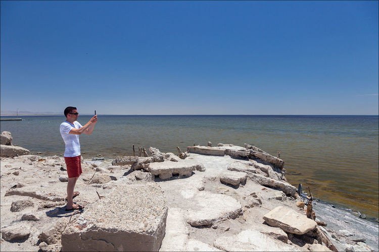 A visitor takes a photo of the salt encrusted shore at bombay beach, a small town situated on the salton sea Blue Casual Clothing Day IPhone Polarized Remote Rock Formation Salton Sea Shopping Shore Sky Standing Tourism Water