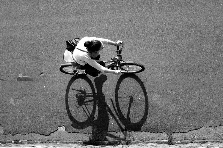 Woman riding bicycle on street, from above