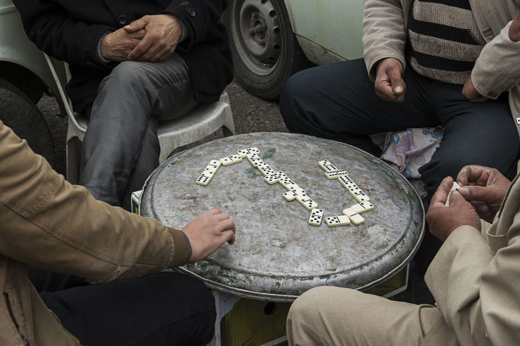 Midsection of men playing with dominoes on metal container