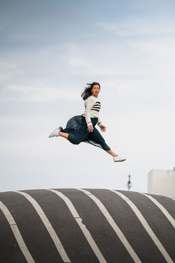 Woman jumping in mid-air against sky