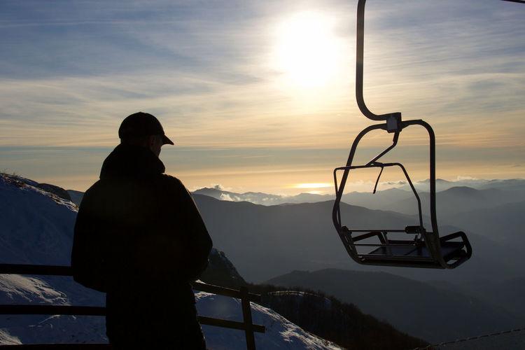 Silhouette man standing against ski lift