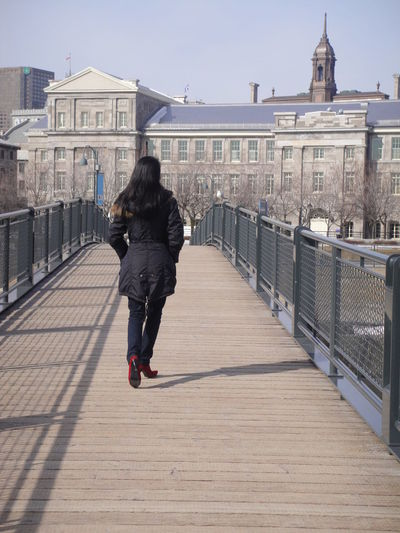Full length rear view of woman walking on footbridge in city
