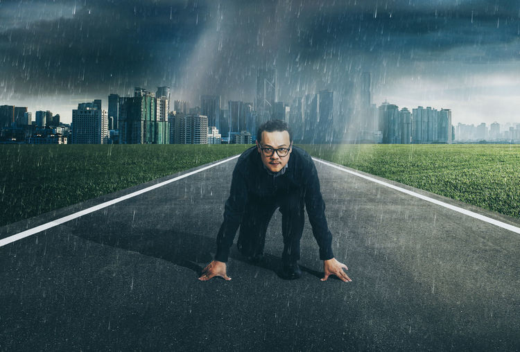 Portrait of businessman kneeling on road against cityscape during rainy season