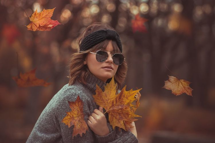 Portrait of woman wearing sunglasses amidst falling maple leaves during autumn