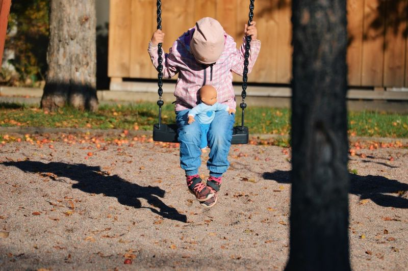Full length of girl with toy playing on swing at playground