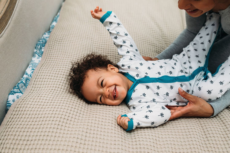 High angle view of mother playing with son on bed at home