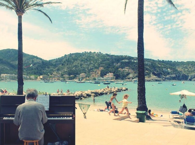 Pianist on the seaside; George Badham Sea Water Sky Enjoyment Leisure Activity Nature Men Real People Lifestyles Mountain Beach Women Sitting Day Beauty In Nature Outdoors People Adult Kids Piano Art Is Everywhere The Great Outdoors - 2017 EyeEm Awards