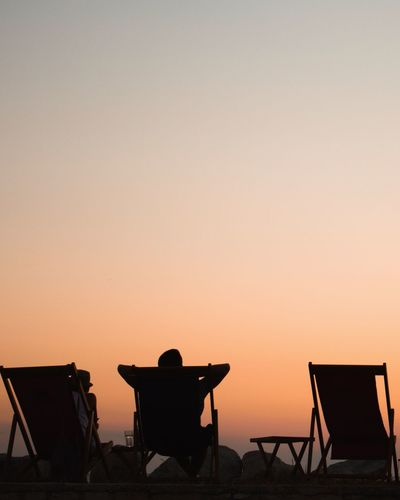 Rear view of people relaxing on deck chairs against clear sky during sunset