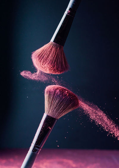 Low angle view of paintbrushes against black background