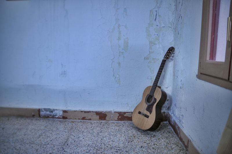 Guitar leaning on wall at home