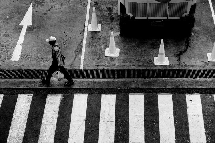 High angle view of man walking by zebra crossing