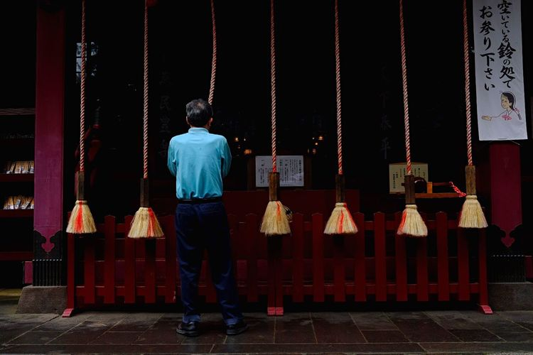 Rear View Of Man Praying While Standing By Huge Tassels At Japanese Temple