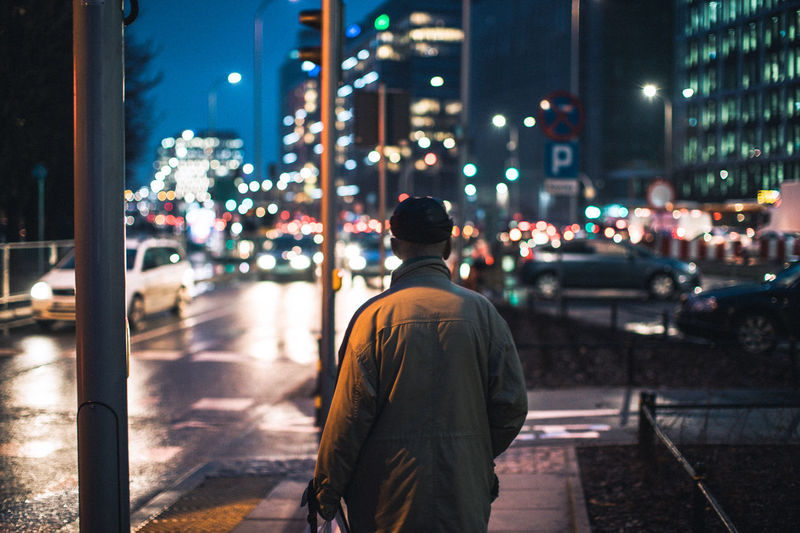 Rear view of a man walking on road at night