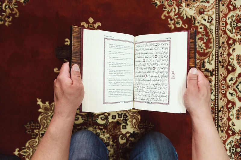 Midsection of man reading koran in mosque