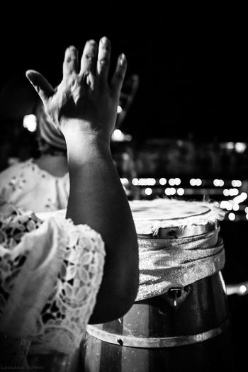 Cropped Hand Of Woman Playing Drum At Night