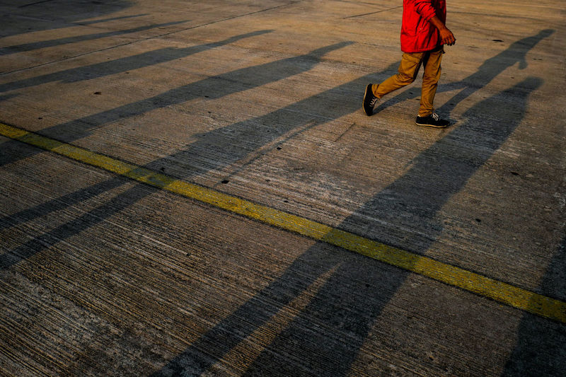 Low section of man walking on street