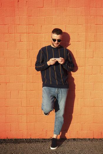 Full length of man standing against brick wall