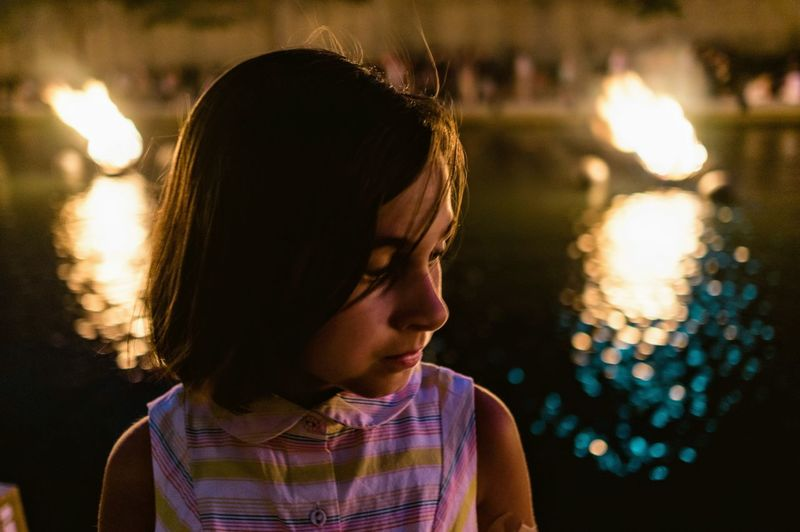 Close-up of girl looking away at night by swimming pool