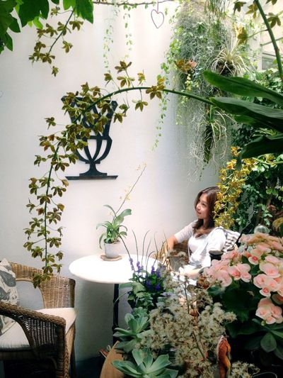 Woman sitting by potted plant on table