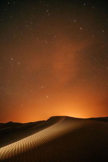 Scenic view of landscape against sky at night in the desert full of stars