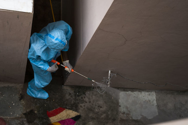 High angle view of worker spraying chemical on walls