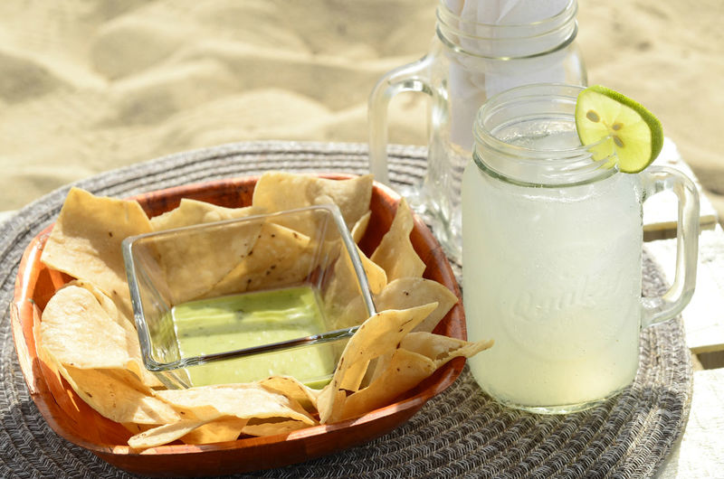 Overhead view of still life green salsa, tortilla chips, lime garnished lemonade baja , mexico