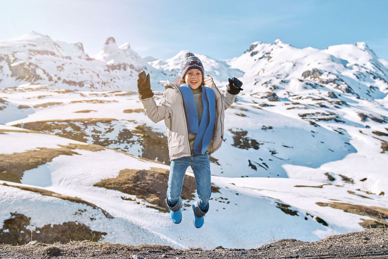 Full length of person standing on snowcapped mountain