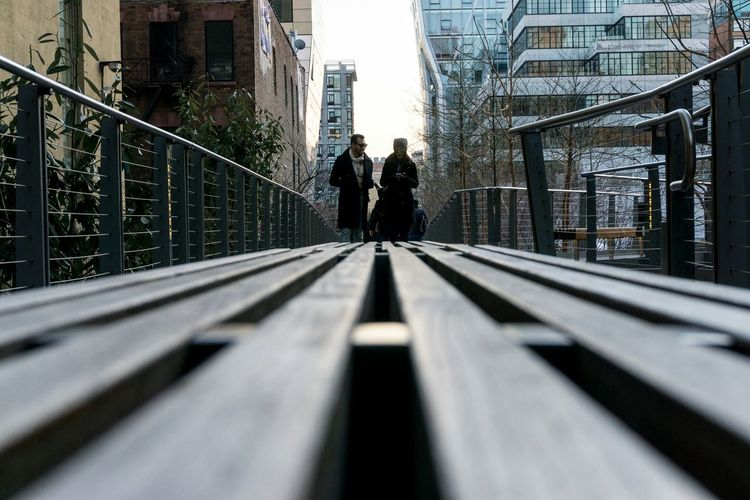 A man and a woman walking the High Line Park on a bright Sunday evening. Photography Leading Lines Depth Of Field People Buildings Trees Park Bench Sunday 365project The Best Of New York