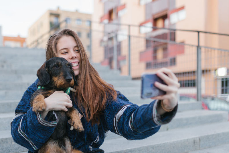 Young woman photographing with dog